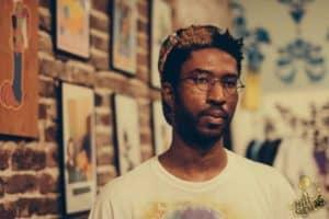 xpayne pop art movement artist against a brick wall lined with photos